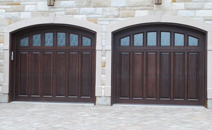 Wooden garage door, Tudor style, Arched with embossed panels and decorative glass, made of solid wood